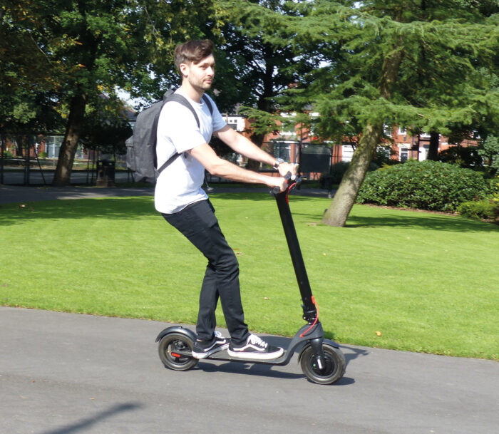 man riding the E10 electric scooter in a park