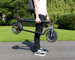 Man holding E10 electric scooter in folded position